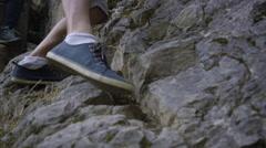 Two Men Climb Down Rocky Terrain Stock Footage