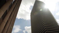 Looking up at some highrise office buildings with sun flare 4k Stock Footage