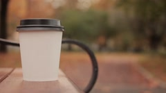 White paper cup with hot drink in autumn city park close up with defocused Stock Footage