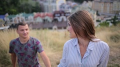 Couple rises up the hill on the background of the city Stock Footage
