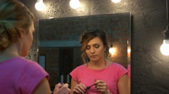 Beautiful young woman checking her face in the mirror Stock Footage