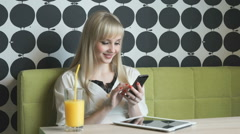Young girl drinking orange juice at the cafe Stock Footage