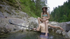 Man Takes Video On Gopro, Relaxing In Natural Hot Spring, Splashes Girlfriend Stock Footage