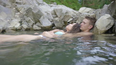 Hikers Relax In A Natural Hot Spring, Man Holds His Girlfriend As She Floats Stock Footage