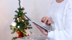 Young Girl Uses Hand Hold Press Tablet on Bokeh Xmas Eve Lights New Year Tree Stock Footage