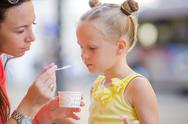 Young mother and her daughters eating ice cream outdoors. Mum feeds his daughter Stock Photos