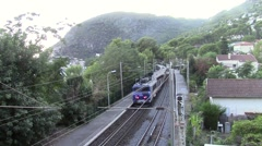 Train leaving a station surrounded by hills Stock Footage