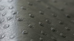 A macro shot of dark gray perforated artificial leather background texture Stock Footage