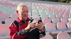 Smiling elderly man with phone. Senior male on a bench. I miss my relatives Arkistovideo