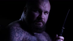 Bald tattoed bearded muscular gangster with a knife. 4K UHD Stock Footage