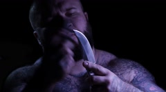 Bald tattoed bearded muscular gangster with a knife and sharpener. 4K UHD Stock Footage
