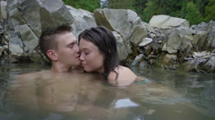 Portrait Of Couple Smiling And Relaxing In Natural Hot Springs, They Kiss Stock Footage