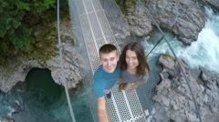 Adventurous Couple Stands On Bridge, Spin In Circle With Gopro, Look Up, Smiling Stock Footage