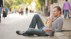 Drunk man lying on the pavement outside. man drinking beer from a paper bag Stock Footage