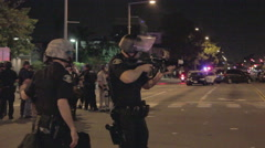 Police aim tear gas gun at rioters - 2012 Anaheim Riots Stock Footage