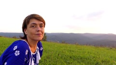 Woman in the Blue Dress Sitting on the Top of Mountain and Resting. Stock Footage