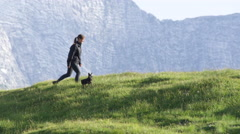 SLOW MOTION: Happy young woman with her small pet dog on hiking adventure Stock Footage