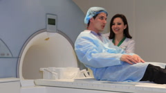 A Lady-Doctor launches an MRI scanner with a patient inside to scan his body Stock Footage