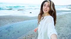 Cute girl pulling her boyfriend asking for walk near sea Stock Footage