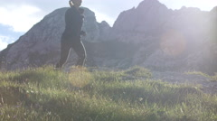 CLOSE UP: Strong young woman running in mountains on magical sunny summer day Stock Footage