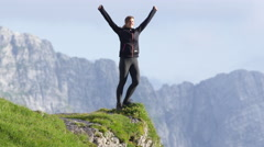 SLOW MOTION: Woman standing on the end of the mountain with her hands high up Stock Footage