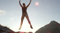 CLOSE UP: Cheerful female standing on rock, jumping, outstretching hands Stock Footage