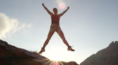 CLOSE UP: Happy female in mountains jumping high and outstretching hands, legs Stock Footage