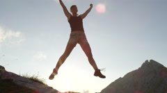 CLOSE UP: Smiling female in mountains jumping high and outstretching hands, legs Stock Footage