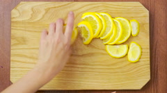 Woman cuts lemon on a wooden board. view from above. top view Stock Footage