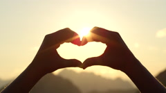 CLOSE UP: Making heart with hands against rising sun and golden morning sky Stock Footage
