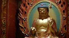 Sculpted image of the Buddha on an altar inside a temple in Singapore Stock Footage