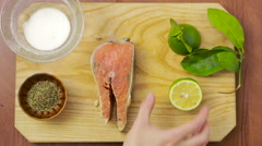 Salmon fillet with lemon lime dill and spices. top view. woman preparing fish Stock Footage