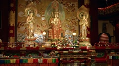 Buddha images stand over a colorful altar inside a temple in Singapore Stock Footage