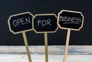OPEN FOR BUSINESS message written with chalk on wooden mini blackboard labels Stock Photos