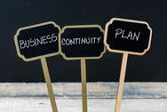 BUSINESS CONTINUITY PLAN message written with chalk on wooden mini blackboard Stock Photos