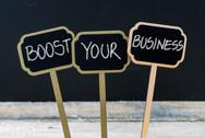 BOOST YOUR BUSINESS message written with chalk on wooden mini blackboard labe Stock Photos