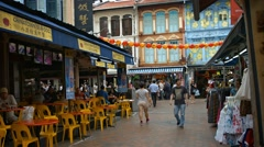 Tourists stroll through past shops and eateries in Singapore Chinatown distri Stock Footage
