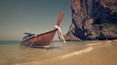 Wooden longtail boat, tied on tropical beach paradise in Thailand, with rocks Stock Footage