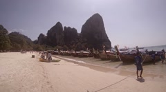 Long line of wooden, longtail tour boats, tied to a tropical beach inThailand Stock Footage