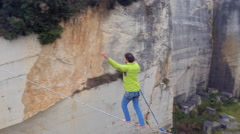 AERIAL: Active guy highlining with backup over quarry and trying to balance Stock Footage