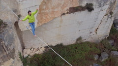 AERIAL: Fearless guy balancing on bouncy slackline tensioned over deep quarry Stock Footage