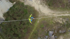 AERIAL: Fearless slackliner sitting on highline over abyss and standing up Stock Footage
