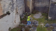 AERIAL: Slackliner balancing on highline, falling and hanging on security rope Stock Footage