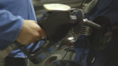 Man puts gas pump back in station Stock Footage