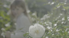 Two girls approach and smell a flower in garden Stock Footage