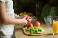Hands cutting the tomatoes, salad on the board Stock Photos