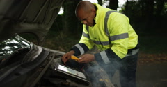 4k, Roadside African American rescue mechanic using tablet to fix car outside. Stock Footage