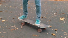 Skater boy picking up skateboard in the autumn park 4K Stock Footage