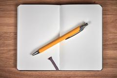 Open notebook and ballpoint on a brown wooden table Stock Photos