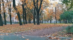 Skater with paper cup walking in the autumn park stands on skateboard and Stock Footage